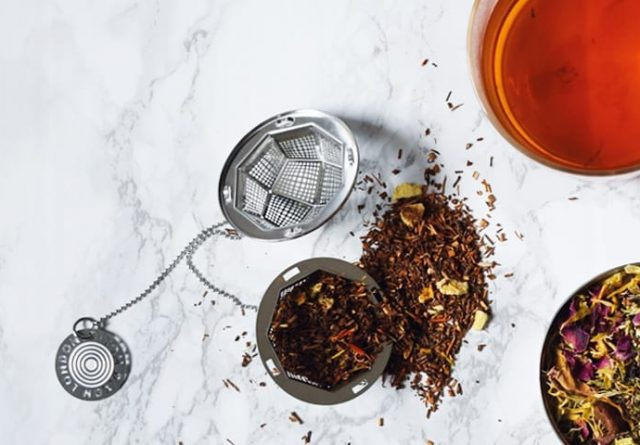 Rooibos tea leaves and a tea infuser on a white marble background