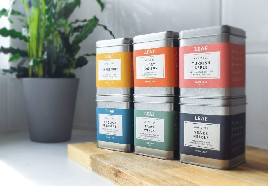 Leaf Tea Shop Loose Leaf Tea Tins on a wooden block with a plant in the background