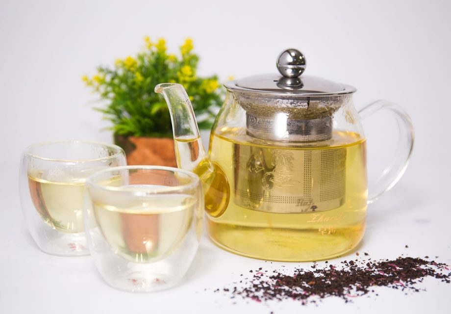 A Tea pot infuser with tea inside and 2 small glasses with tea inside