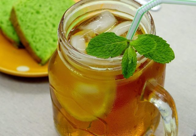Lemon Iced Tea in a glass container and green cake in the background