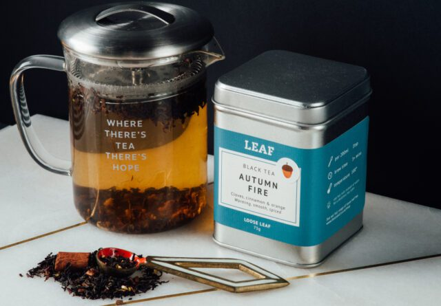 Autumn Fire Tea Tin with Tea Leaves on a marble surface sitting next to a Leaf Teapot