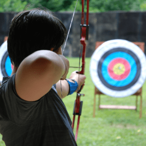 Someone aiming a bow and arrow at a target