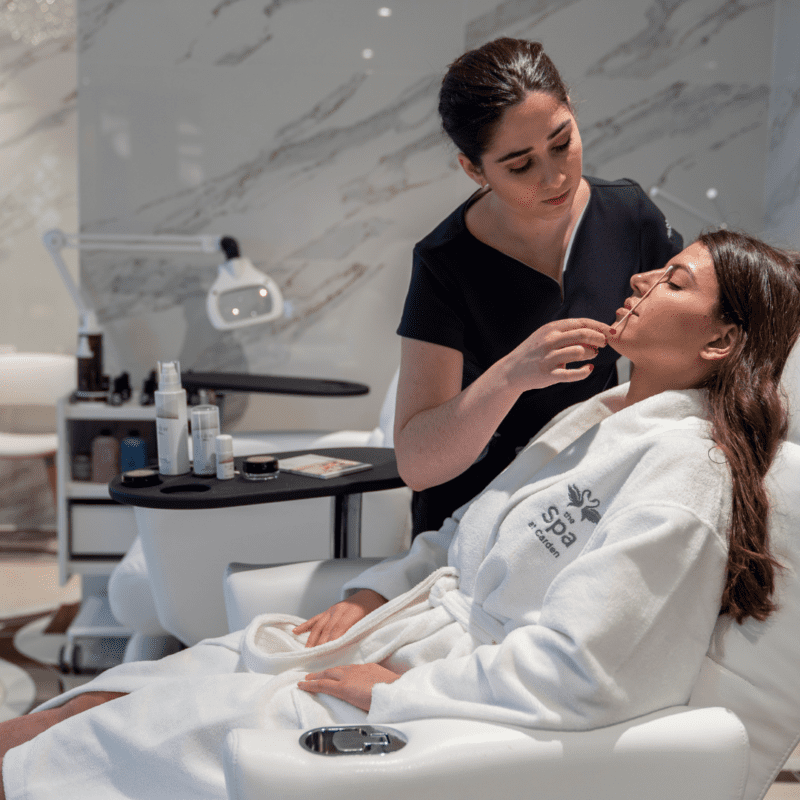 Spa therapist doing treatment on face