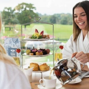 A woman enjoying the afternoon tea with a glass of champagne