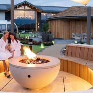 A couple sat at the outdoor fire pit