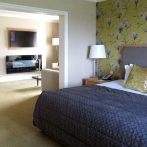A bed in a large hotel room at Carden park