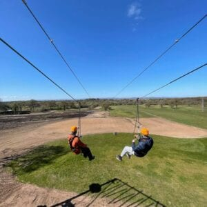 Two people doing the zipline on Carden Parks Pusuits adventure park