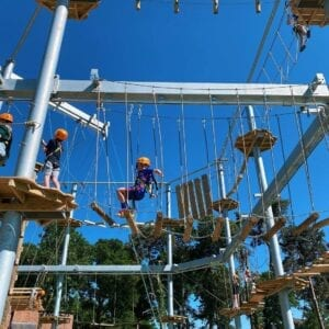 Three people attempting to do the Pursuits adventure course