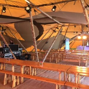 People setting up tables, ready for an event in the tent