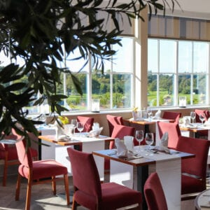A restaurant in the Carden Park Hotel with red chairs