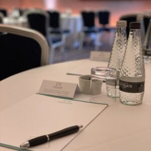 Two bottles of water with a pad of paper and pen on a conference room table