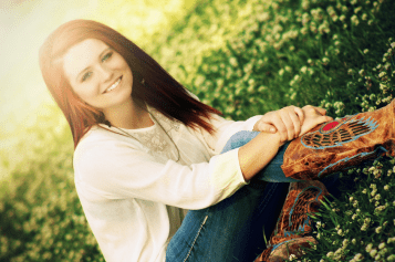 A red haired  girls in a field of flowers