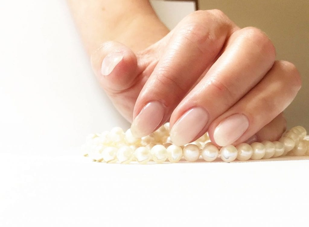 A zoomed in image of a persons hand with a pearl necklace