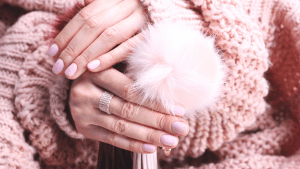 Two hands with pink nails and pink jumper